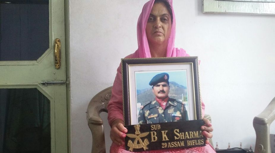 Aruna Devi holds the picture of her husband, martyr Baldev Kumar Sharma, at her home in Marura village near Shahtalai in Bilaspur (PHOTO: SNS)