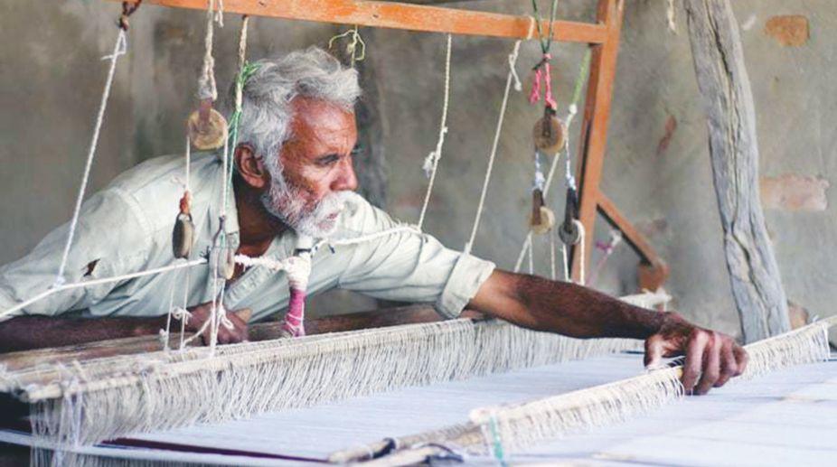 An old villager binds threads on the khaddi.