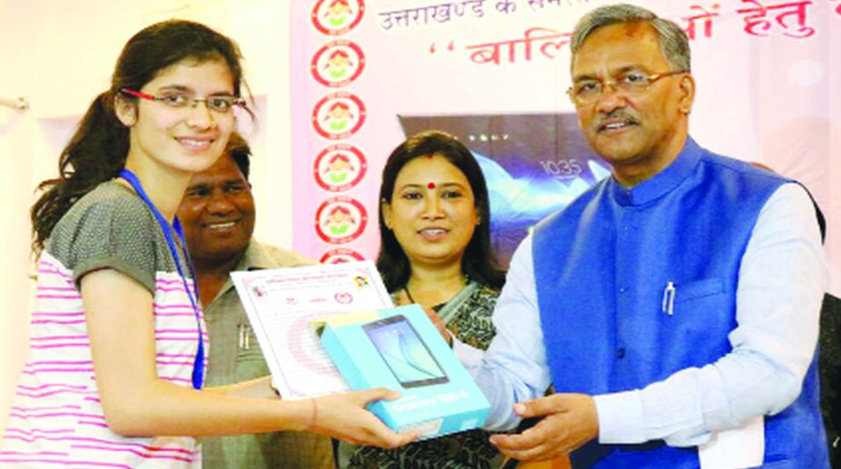 Uttarakhand Chief Minister Trivendra Rawat presenting a tablet to a girl in Dehradun on Wednesday.