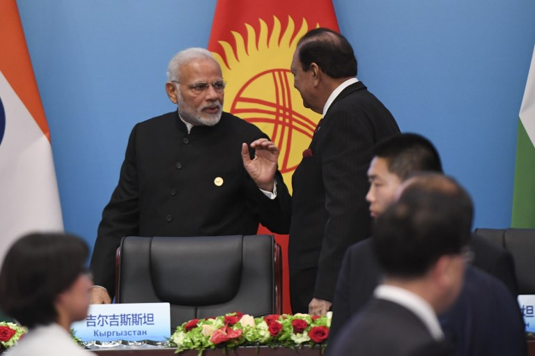 Prime Minister, Narendra Modi talks with Pakistan's President Mamnoon Hussain after a signing ceremony during the Shanghai Cooperation Organisation (SCO) Summit in Qingdao on June 10, 2018.