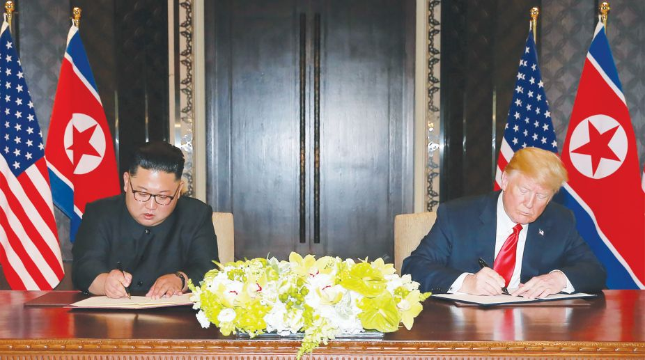 "In this picture taken on June 12, 2018 and released from North Korea's official Korean Central News Agency (KCNA) on June 13, 2018, US President Donald Trump (R) and North Korea's leader Kim Jong Un (L) sign documents at a signing ceremony during their historic US-North Korea summit, at the Capella Hotel on Sentosa island in Singapore. / AFP PHOTO / KCNA VIA KNS / - / South Korea OUT / REPUBLIC OF KOREA OUT ---EDITORS NOTE--- RESTRICTED TO EDITORIAL USE - MANDATORY CREDIT ""AFP PHOTO/KCNA VIA KNS"" - NO MARKETING NO ADVERTISING CAMPAIGNS - DISTRIBUTED AS A SERVICE TO CLIENTS / THIS PICTURE WAS MADE AVAILABLE BY A THIRD PARTY. AFP CAN NOT INDEPENDENTLY VERIFY THE AUTHENTICITY, LOCATION, DATE AND CONTENT OF THIS IMAGE. /"