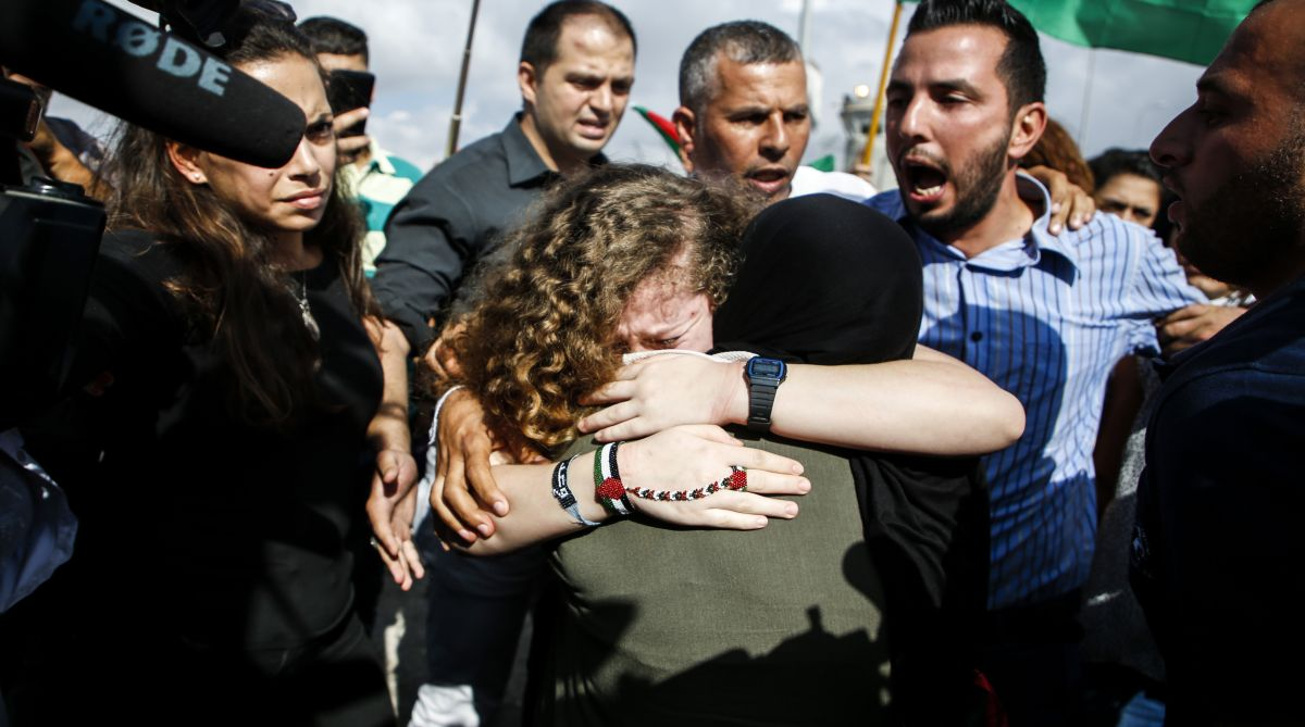 Palestinian activist and campaigner Ahed Tamimi (C) embraces a woman upon her release from prison. Picture | AFP PHOTO / ABBAS MOMANI