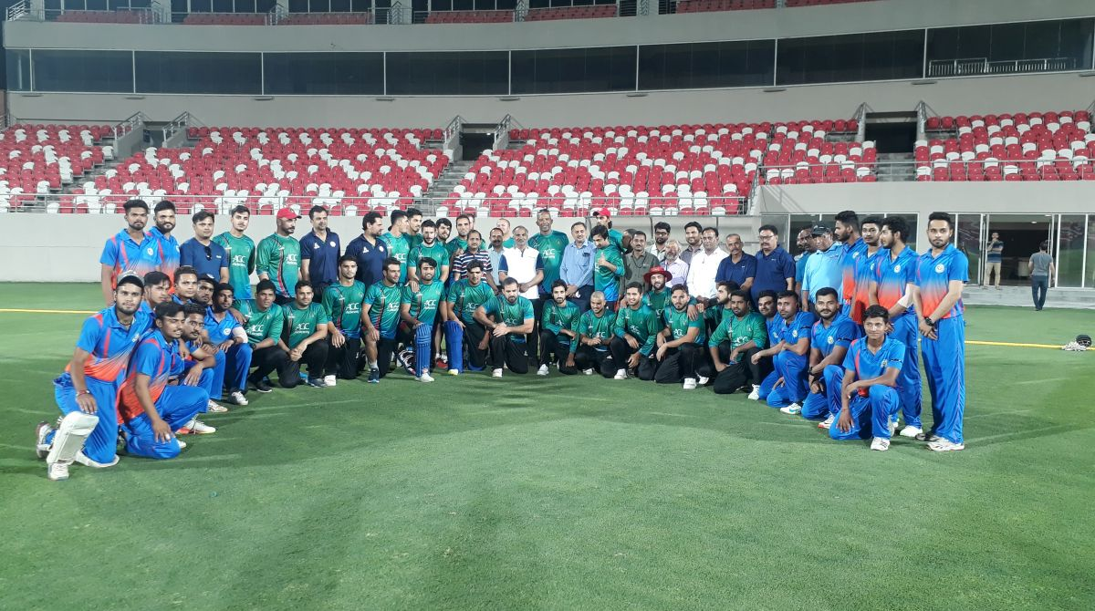 A group photo of the Afghanistan and Uttarakhand cricket team.
