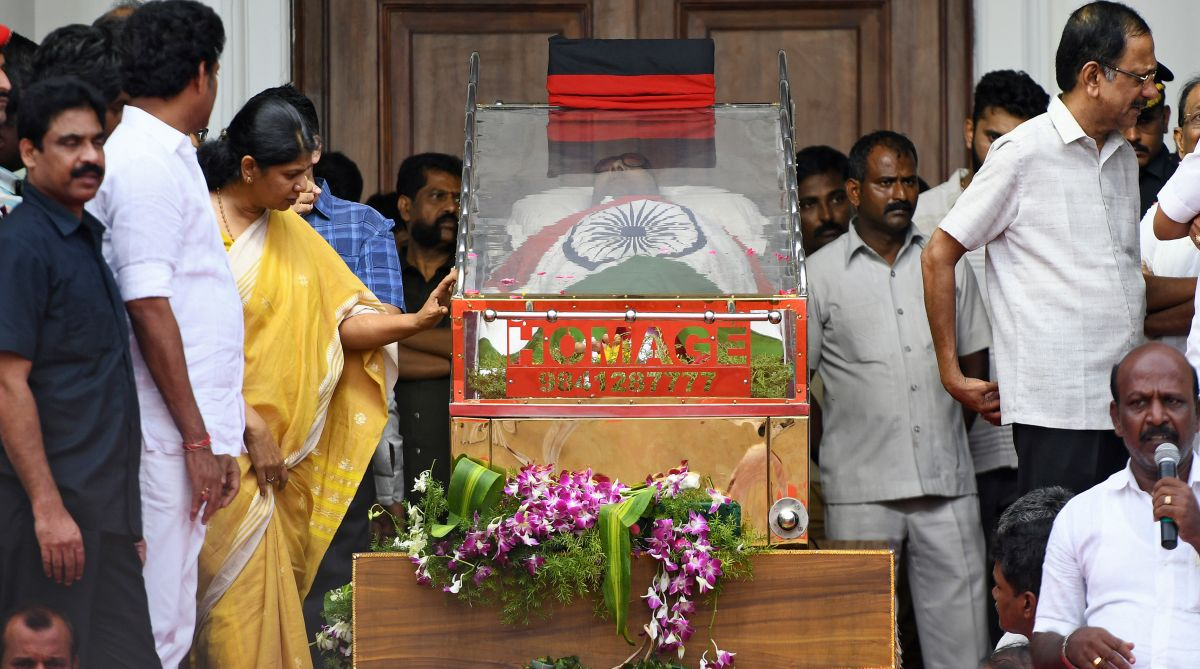 Indian MP Kannimozhi (3rd L in yellow) of the Dravida Munnetra Kazhagham (DMK) party looks at the body of her father and DMK party president Muthuvel Karunanidhi. AFP PHOTO / Arun SANKAR