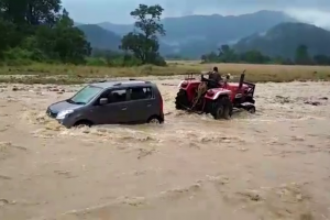 Watch how a tractor saved lives of teachers by pulling their car out from swollen Nainital stream